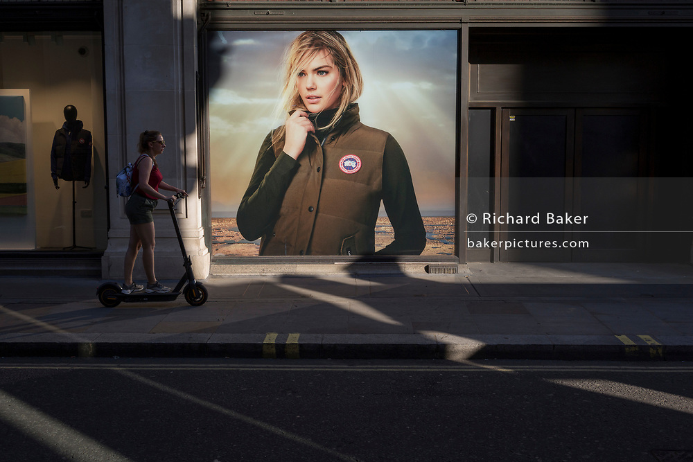 With a further 154 UK covid deaths reported in the last 24hr, bringing the total to 43,081 victims during the Coronavirus pandemic, the easing of government lockdown restrictions for the re-opening of shops continues and a lady scoots past a billboard for Canada Goose on Little Argyll Street, on 24th June, in London, England.