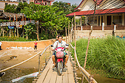 09 MARCH 2013 - VANG VIENG, LAOS:  A motorcyclists crosses the Nam Song River on a temporary bamboo bridge in Vang Vieng, Laos. The bridge is only used in the dry season. It washes away when the river rises during the rainy season and rebuilt when the river recedes. PHOTO BY JACK KURTZ