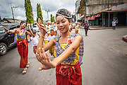 31 OCTOBER 2012 - YALA, YALA, THAILAND:  Villagers from Wat Kohwai dance as they process through Yala for Ok Phansa. Ok Phansa marks the end of the Buddhist 'Lent' and falls on the full moon of the eleventh lunar month (October). It's a day of joyful celebration and merit-making. For the members of Wat Kohwai, in Yarang District of Pattani, it was a even more special because it was the first time in eight years they've been able to celebrate Ok Phansa. The Buddhist community is surrounded by Muslim villages and it's been too dangerous to hold the boisterous celebration because of the Muslim insurgency that is very active in this area. This the year the Thai army sent a special group of soldiers to secure the village and accompany the villagers on their procession to Yala, a city  about 20 miles away.  PHOTO BY JACK KURTZ