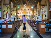 15 FEBRUARY 2015 - BANGKOK, THAILAND:  A woman walks into Santa Cruz Catholic Church in the Kudeejeen neighborhood in Bangkok. Santa Cruz church was established in 1770  and is one of the oldest and most historic Catholic churches in Thailand. The church was originally built by Portuguese soldiers allied with King Taksin the Great. Taksin authorized the church as a thanks to the Portuguese who assisted the Siamese during the war with Burma. Most of the Catholics in the neighborhood trace their family roots to the original Portuguese soldiers who married Siamese (Thai) women. There are about 300,000 Catholics in Thailand in about 430 Catholic parishes and about 660 Catholic priests in Thailand. Thais are tolerant of other religions and although Thailand is officially Buddhist, Catholics are allowed to freely practice and people who convert to Catholicism are not discriminated against.     PHOTO BY JACK KURTZ