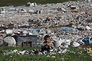 Roma Gypsy boy playing amongst used paint spray aerosol cans nearby the municipal dumpsite, where many thousand Roma Gypsies earn their living recycling, outside Dallas, and Cluj-Napoca in Romania