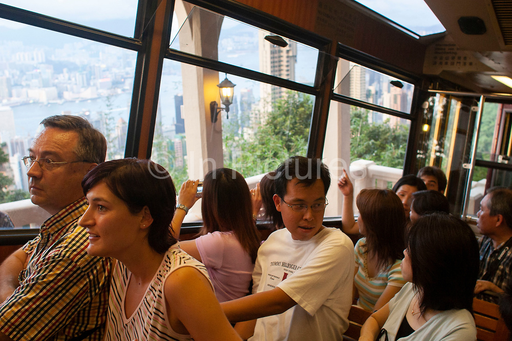Passengers on the famous Peak Tram which takes mainly tourists from Central Hong Kong up to the Victoria Peak viewing platform in Hong Kong, China. The Peak Tram is a funicular railway in Hong Kong, which carries both tourists and residents to the upper levels of Hong Kong Island.