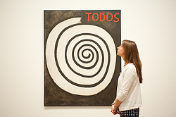 """Mira Schendel at Tate Modern in London. <br /> Tate Modern employee poses next to works entitled """"Untitled (All) 1964"""" by Mira Schendel, Tate Modern, London, Tuesday, 24th September 2013. Picture by Piero Cruciatti / i-Images"""