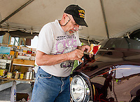 """Russ Mowry of Candia works on a """"bagger"""" Harley Davidson at his pinstriping tent in front of Thurston's Marine at Weirs Beach Thursday afternoon.  (Karen Bobotas/for the Laconia Daily Sun)"""