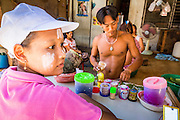 30 APRIL 2013 - MAHACHAI, SAMUT SAKHON, THAILAND:   A Burmese teenaged girl waits to buy betel from a Burmese betel vendor in the Thai fishing port of Mahachai. The girl works in a fish processing plant and chews the betel, which is a mild stimulant. The Thai fishing industry is heavily reliant on Burmese and Cambodian migrants. Burmese migrants crew many of the fishing boats that sail out of Samut Sakhon and staff many of the fish processing plants in Samut Sakhon, about 45 miles south of Bangkok. Migrants pay as much $700 (US) each to be smuggled from the Burmese border to Samut Sakhon for jobs that pay less than $5.00 (US) per day. There have also been reports that some Burmese workers are abused and held in slavery like conditions in the Thai fishing industry. Thanaka powder has been used by Burmese for over 2000 years for protection from the sun.         PHOTO BY JACK KURTZ
