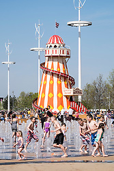 Helter Skelter funfair and fountain with many visitors at Queen Elizabeth Olympic Park in Stratford London United Kingdom