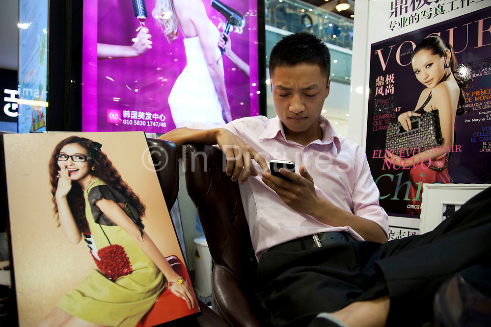 Man surrounded by pictures of beautiful women at a portrait photography stall  inside the New world Shopping Mall in Beijing, China. Beijing New World Shopping Mall on Chongmenwen Wai Street covers a total area of 70,000 sq. m. It is one of the most popular shopping centres in Chongwen district Beijing. This elegantly decorated department store offers each visitor very considerate service, comfortable shopping environment and enough choices of worldwide famous brands.