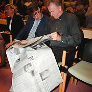 Raadvergadering gemeente Huizen nieuwbouw Flevoschool, publiek leest krant