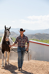 handsome cowboy with a Paint Horse on a ranch