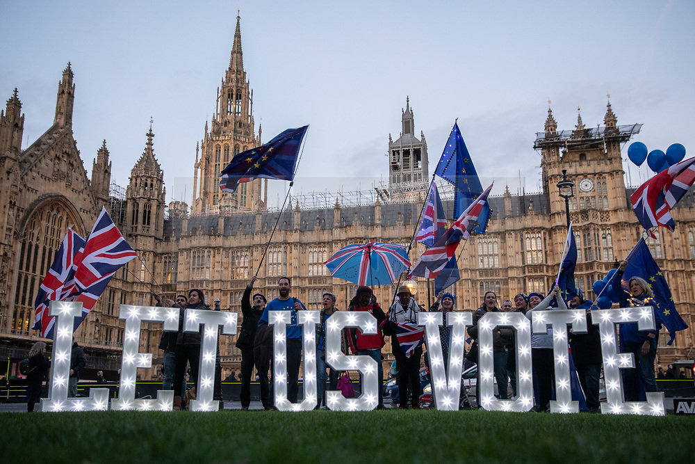 """© Licensed to London News Pictures. 27/03/2019. London, UK. Campaigning group Avaaz install 1.2 metre-tall illuminated letters spelling out """"LET US VOTE"""" outside the Houses of Parliament. This evening MPs are expected to vote on a series of indicative votes on alternative proposals to British Prime Minister Theresa May's withdrawal agreement. Photo credit : Tom Nicholson/LNP"""