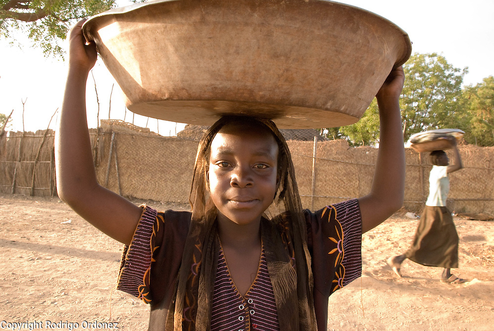 A girl carries a bucket on her head in the town of Abyei.