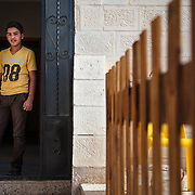 """Ab al Kareem, 14, and his family arrived in Jordan two years ago, after fleeing the Syrian conflict. is a participant in the Nubader No Lost Generation Project at Mercy Corps' partner organization AJDT. The No Lost Generation Project aims to provide at risk Syrian and Jordanian youth with alternative education, skills, and psychosocial services to address profound stress the children have gone through. He just finished the sports program and hopes to attend another session at the center. <br /> <br /> He's wearing the clothes he was wearing when he crossed the border from Syria to Jordan. He crossed the border with only the clothes on his back. """"The clothes remind me of Syria, that's why they are important to me."""" Mafraq, Jordan, May 2015."""
