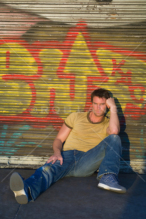 Man in causal clothes sitting in front of a graffiti storefront