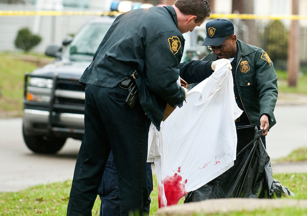 Matt Dixon | The Flint Journal..Flint police collect evidence at the scene of a shooting on W. Paterson and Mason Streets in Flint Friday Evening.The victim was taken to Hurley Medical Center in serious condition.