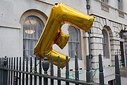 An E balloon representing the concept of remaining in Europe blows in the wind on railings during a pro-EU brexit protest opposite Parliament, on 11th March 2019, in Westminster, London, England.