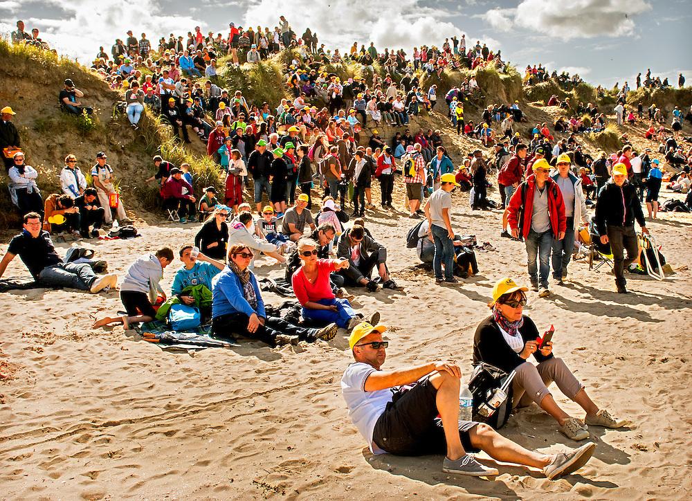 Frankrijk, Utah Beach, 02-07-2016<br /> Wielrennen, Tour de France, 1e etappe.<br /> Van Mont-Saint-Michel naar Utah Beach.<br /> De Tour fan's, met hun gele petjes op, zitten na afloop van de huldigingsceremonie op Utah Beach, één van de stranden waar in 1944 de invasie in Normandie van de geallieerden plaatsvond. <br /> Foto: Klaas Jan van der Weij