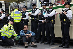 London, UK. 31st August, 2021. A Metropolitan Police officer arrests an environmental activist from Extinction Rebellion who had glued himself to the road after a vintage bus was used as base to block a road junction to the south of London Bridge on the ninth day of Impossible Rebellion protests. Extinction Rebellion are calling on the UK government to cease all new fossil fuel investment with immediate effect.