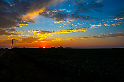 Sunset with corn field, soybean field, rural road and oil terminal silhouetted in the foreground.
