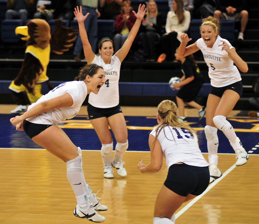Halley Viola (left), Terri Angst (4), Ashlee Fisher (5), and Caryn Mastandrea (15), celebrate after scoring a point in a game against St. John's University, Friday Oct. 3 2008. The Golden Eagles won 3-1.