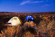 A pair of tents glow in the twilight in the campground at Sand Hollow State Park, Utah. The park, one of the newest and most popular of the state, showcases sand dunes and an attractive desert reservoir.