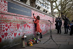 © Licensed to London News Pictures. 08/04/2021. London, UK. Fran Hall, a member of COVID-19 Bereaved Families for Justice, draws the final heart marking the completion of the approximately 150,000 hearts being painted onto the National Covid Memorial Wall on the Thames Embankment opposite the Houses of Parliament. Campaigners are asking Prime Minister Boris Johnson to make the memorial permanent. Photo credit: Rob Pinney/LNP