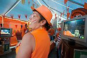 Een vrouw zingt uit volle borst het Nederlandse volkslied mee bij het begin van de WK finale. In een grote tent aan de Royaards van den Hamkade in de Utrechtse volkswijk Ondiep, de wijk waar Wesley Sneijder vandaan komt, kijkt een grote groep oranjesupporters naar de wedstrijd.<br /> <br /> A woman is singing the national hymn at the start of the finals of the World Championship Soccer 2010.