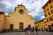 Young people walk by the Basilica di Santo Spirito, Florence