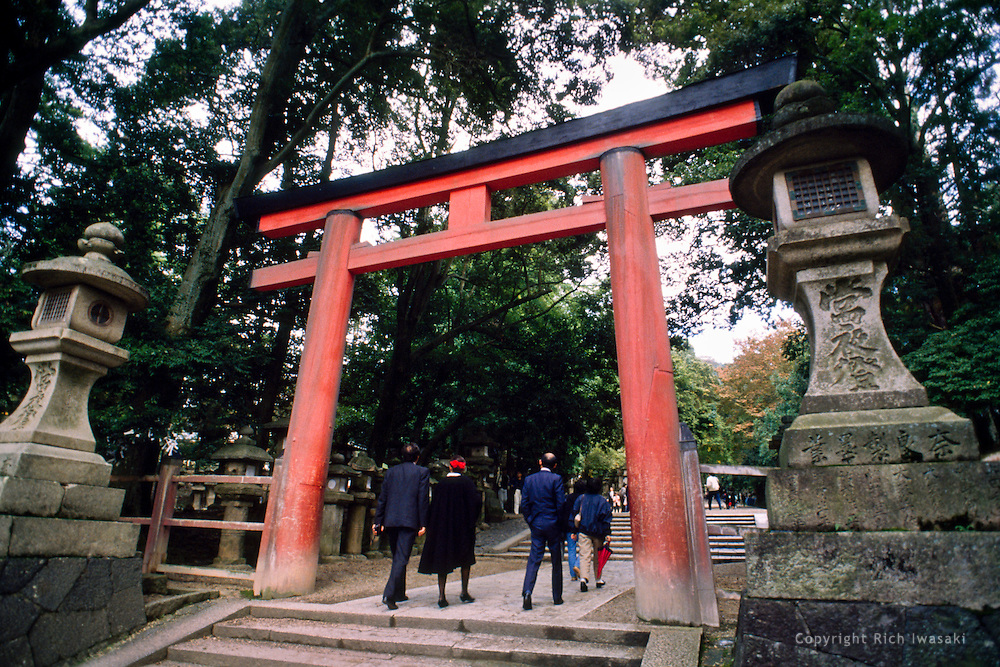 Visitors walk under torii (gateway) at entrance to shrine in Nara, Nara Prefecture, Japan