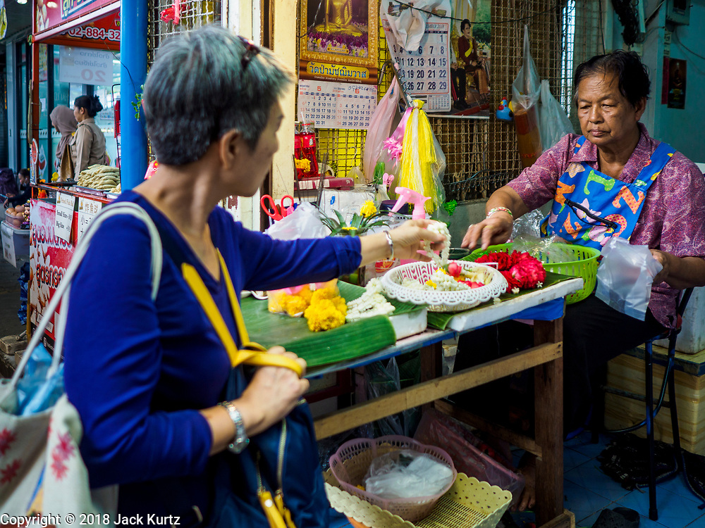 17 SEPTEMBER 2018 - BANGKOK, THAILAND: A woman buys a flower garland from a vender who makes and sells flower garlands in a small shop in Klong San market, next to the ICONSIAM development. ICONSIAM is a mixed-use development on the Thonburi side of the Chao Phraya River. It is expected to open in 2018 and will include two large malls, with more than 520,000 square meters of retail space, an amusement park, two residential towers and a riverside park. It is the first large scale high end development on the Thonburi side of the river and will feature the first Apple Store in Thailand and the first Takashimaya department store in Thailand. Rents for shopkeepers in Klong San market can be up to 30,000 Thai Baht per month (about $920US) and some in Bangkok are concerned that Klong San Market will lose its local character when the huge mall opens.      PHOTO BY JACK KURTZ