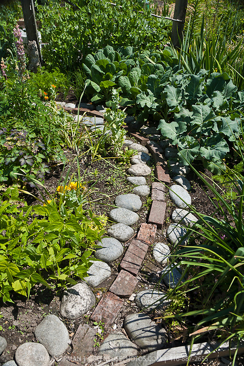 Large pebbles and old brick combined to make a garden path and planting bed edging.