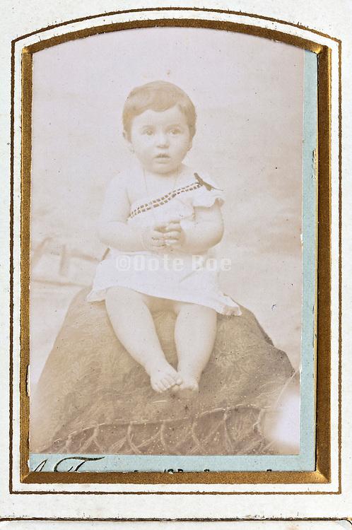 fading studio 1900s portrait of toddler wit golden passe-partout