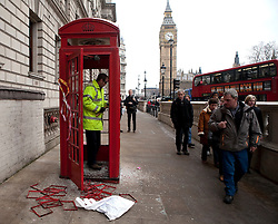(c) London News Pictures. 10.12.2010. A worker repairs a red phonebox in Parliament Square. The clean-up operation in Westminster following last night's student demonstration. Picture credit should read: Fuat Akyuz/London News Pictures