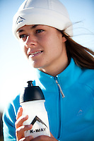 Brunette wearing sportswear and beanie on head. holding bottle with water. fitness concept