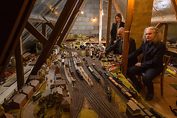 Brothers Simon, 53 and Paul Hurst, 58 have some of their late father's ashes carried around his extensive model railway in the loft of his home. PICTURED: Paul's wife Lois, Paul and Simon, right, in the loft with their their father's model railway. Leeds, Kent, March 15 2018.