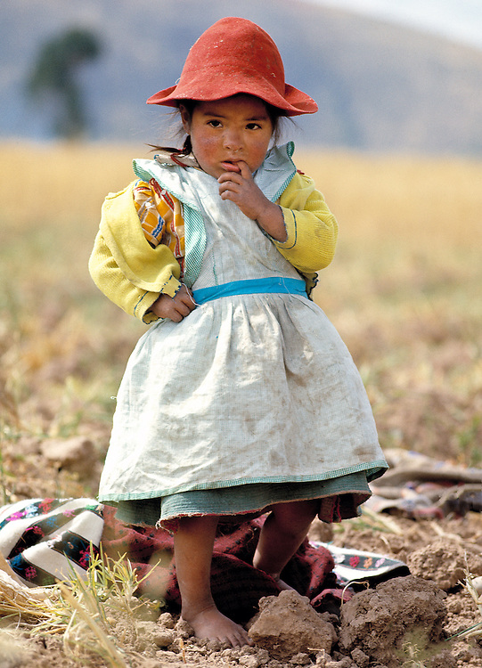 A pensive child eyes the camera near a potato harvest in the Altiplano in Peru.
