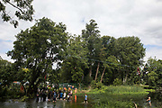 Environmental activists from HS2 Rebellion, including Swan l and Larch r on a line above the shallow river Colne in Denham Country Park, attempt to protect an ancient alder tree from destruction in connection with works for the HS2 high-speed rail link on 24th July 2020 in Denham, United Kingdom. A large security operation involving officers from the Metropolitan Police, Thames Valley Police, City of London Police and Hampshire Police as well as the National Eviction Team ensured the removal of the tree by HS2 despite the protests by activists.
