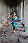 An woman dressed in the costume of a traditional Khmer spirit, the Apsara, walking through the cloisters, Angkor Wat, Siem Reap, Cambodia
