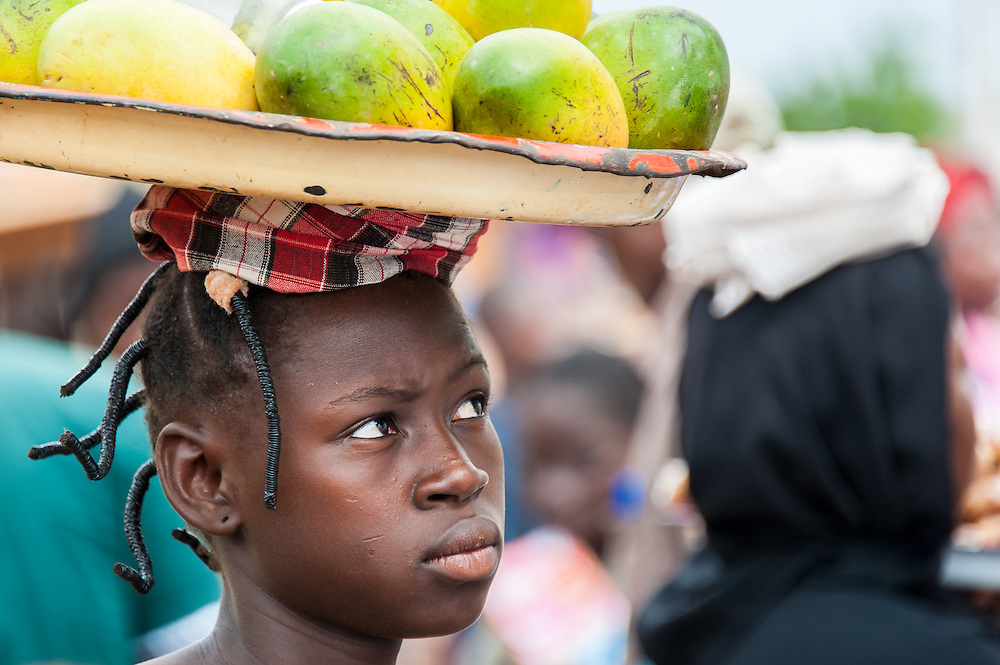 Portrait of a young Burkinabe girl selling mangoes in a local farmer's market in central Burkina Faso