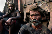 Railway workers shovel coal in a Varanasi rail yard