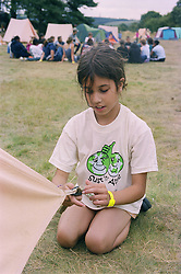 Girl sitting on grass in campsite assembling tent during environmental awareness camp,