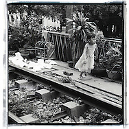 A little girl runs along the railway of Hanoi. She wears a princess dress. Along the railway, a cage with a cat inside and some green plants.