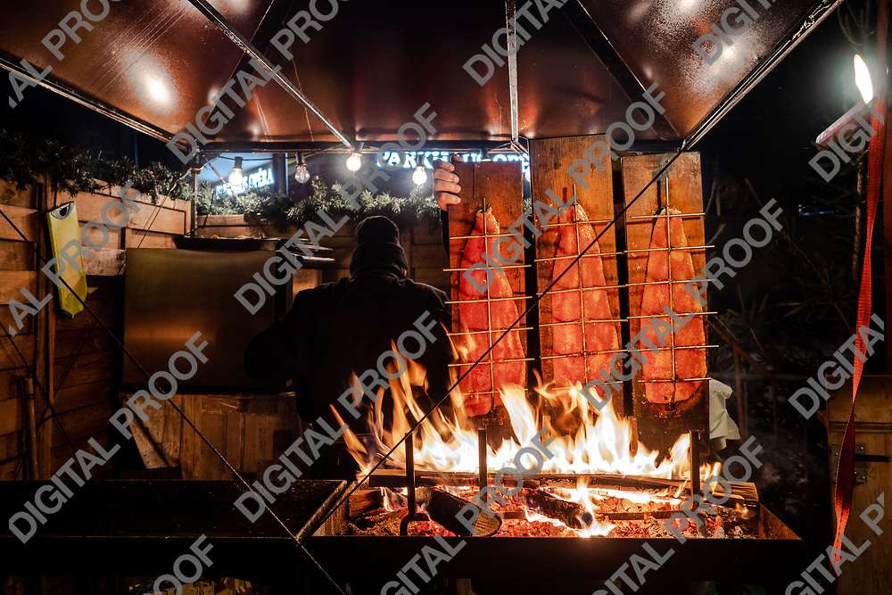 Zurich, Switzerland - December 22, 2018 Salmons are being smoked - cooked with wood planks in a food stand of the Christmas market held at Sechseläutenplatz