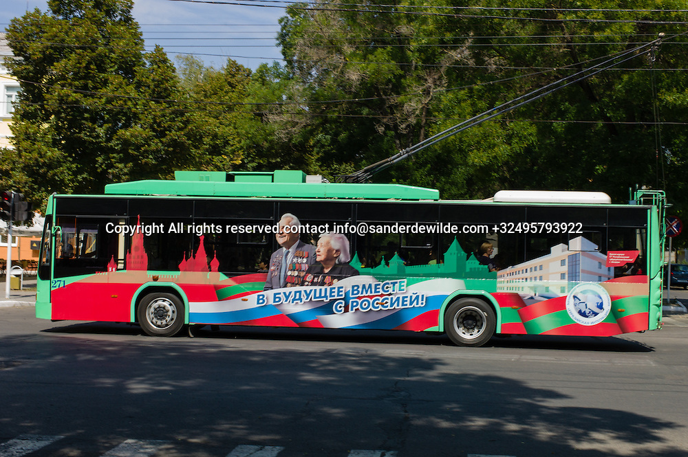 20150826  Moldova, Transnistria, Tiraspol. A green Trollybus , apparently a gift of Russia, is stickered with a typical image of elderly people and national Transnistrian and Russian signs and colors, saying: we belong together