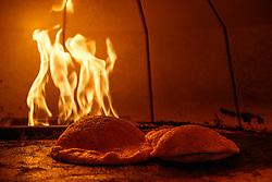 Flabread baking in oven in front of flames, Atico, Fort Worth, Texas, USA. Atico is a Spanish tapas bar atop a Stockyards hotel and is owned by Tim Love.
