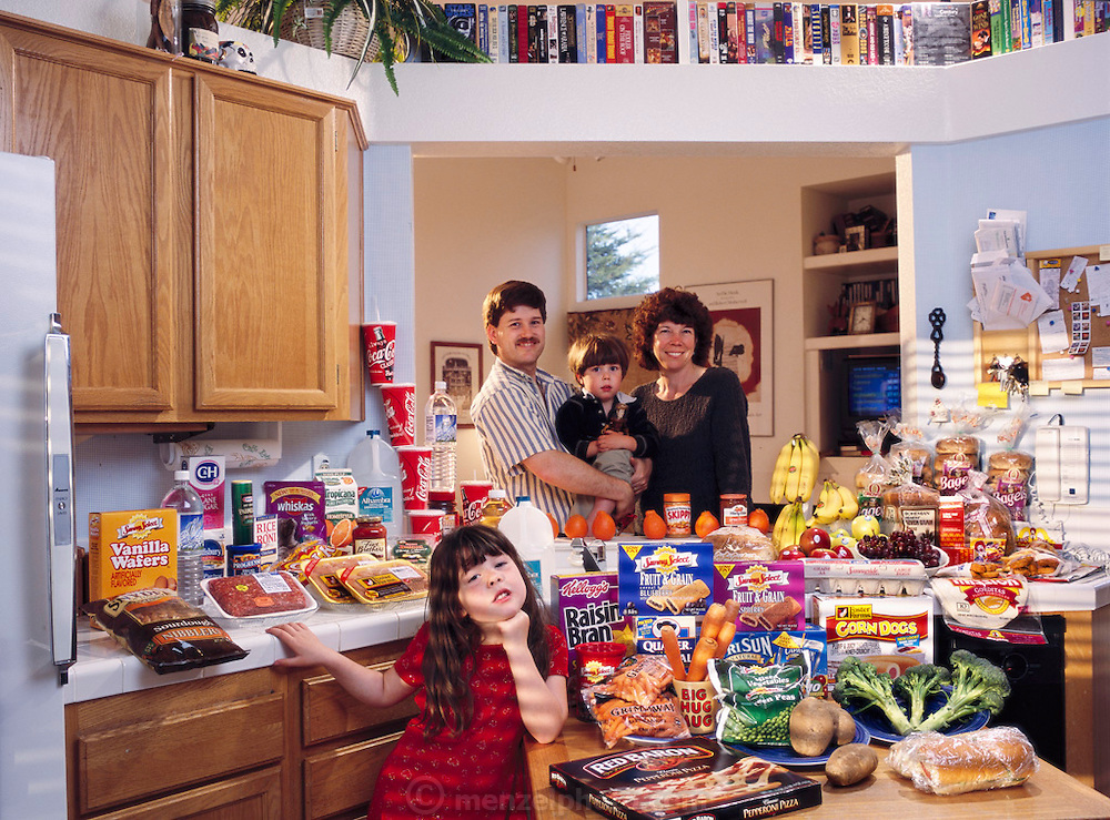(MODEL RELEASED IMAGE). The Caven family in the kitchen of their home in American Canyon, California, with a week's worth of food. Craig Caven,  and Regan Ronayne, (holding Ryan), stand behind the kitchen island; in the foreground is Andrea. The Caven family is one of the thirty families featured in the book Hungry Planet: What the World Eats (p. 260).