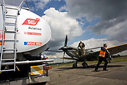 "A Supermarine Spitfire awaits refuelling with Avgas 100LL fuel at Farnborough International Airshow media launch. The pilot is the air show's Flight Operations Director Rod Dean who stands on the wing of this old WW2 warbird fighter of the British Royal Air Force and the refueller man has unhooked the nozzle from the bowser and hauls it across the concrete towards the aircraft. Hazardous and flammable signs are on the truck's rear. Avgas 100LL is a fuel designed for piston engines and is the most commonly used aviation fuel, dyed blue for easy visual identification. 100LL, spoken as ""100 low lead"", contains a small amount of tetra-ethyl lead (TEL), a lead compound that reduces gasoline's tendency to spontaneously explode (detonation or ""knock"") under high loads, high temperatures and high pressures - perfect for aerobatic performance flying."