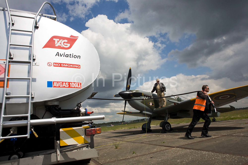 """A Supermarine Spitfire awaits refuelling with Avgas 100LL fuel at Farnborough International Airshow media launch. The pilot is the air show's Flight Operations Director Rod Dean who stands on the wing of this old WW2 warbird fighter of the British Royal Air Force and the refueller man has unhooked the nozzle from the bowser and hauls it across the concrete towards the aircraft. Hazardous and flammable signs are on the truck's rear. Avgas 100LL is a fuel designed for piston engines and is the most commonly used aviation fuel, dyed blue for easy visual identification. 100LL, spoken as """"100 low lead"""", contains a small amount of tetra-ethyl lead (TEL), a lead compound that reduces gasoline's tendency to spontaneously explode (detonation or """"knock"""") under high loads, high temperatures and high pressures - perfect for aerobatic performance flying."""