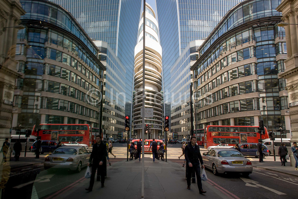 A symmetrical scene of London city workers out walking and shopping at lunchtime, with tall office buildings rising above. Seen parallel to a large retailer's front window, the world beyond is seen as a mirror image, duplicating left and right halves, to show the capital's financial and oldest district, as a double picture. A man walks along the street in the foreground while a bus passes-by on the background - duplicated as if there are two.