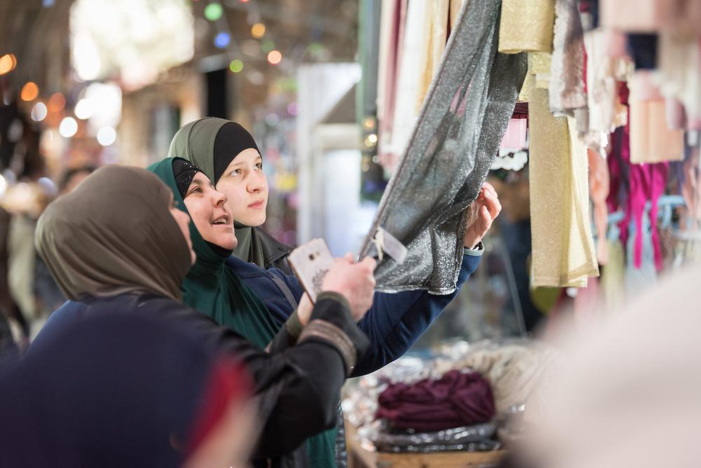 19 April 2019, Jerusalem: Women inspect a piece of cloth at the Suq al Qattanin (the Cotton Market).
