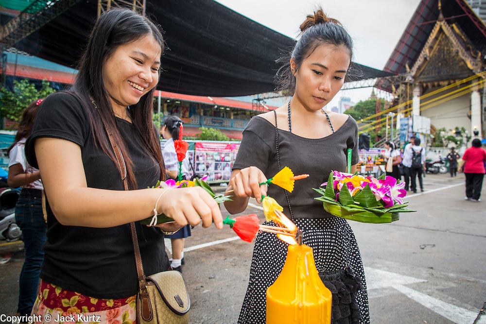 28 NOVEMBER 2012 - BANGKOK, THAILAND: People light the candles and incense on their krathongs before placing them in the Chao Phraya River on Loy Krathong at Wat Yannawa in Bangkok. Loy Krathong takes place on the evening of the full moon of the 12th month in the traditional Thai lunar calendar. In the western calendar this usually falls in November. Loy means 'to float', while krathong refers to the usually lotus-shaped container which floats on the water. Traditional krathongs are made of the layers of the trunk of a banana tree or a spider lily plant. Now, many people use krathongs of baked bread which disintegrate in the water and feed the fish. A krathong is decorated with elaborately folded banana leaves, incense sticks, and a candle. A small coin is sometimes included as an offering to the river spirits. On the night of the full moon, Thais launch their krathong on a river, canal or a pond, making a wish as they do so.    PHOTO BY JACK KURTZ